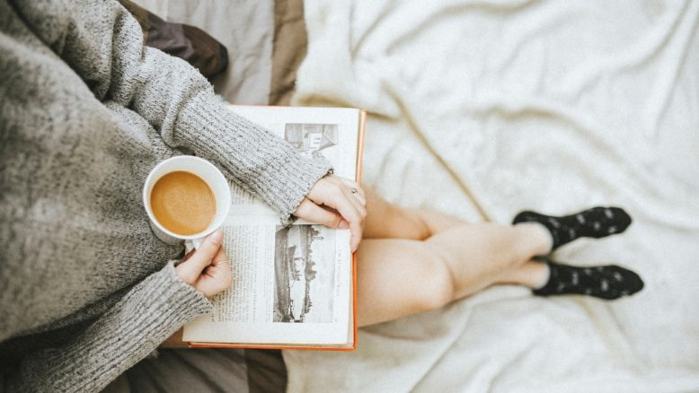 Reading book with hot drink